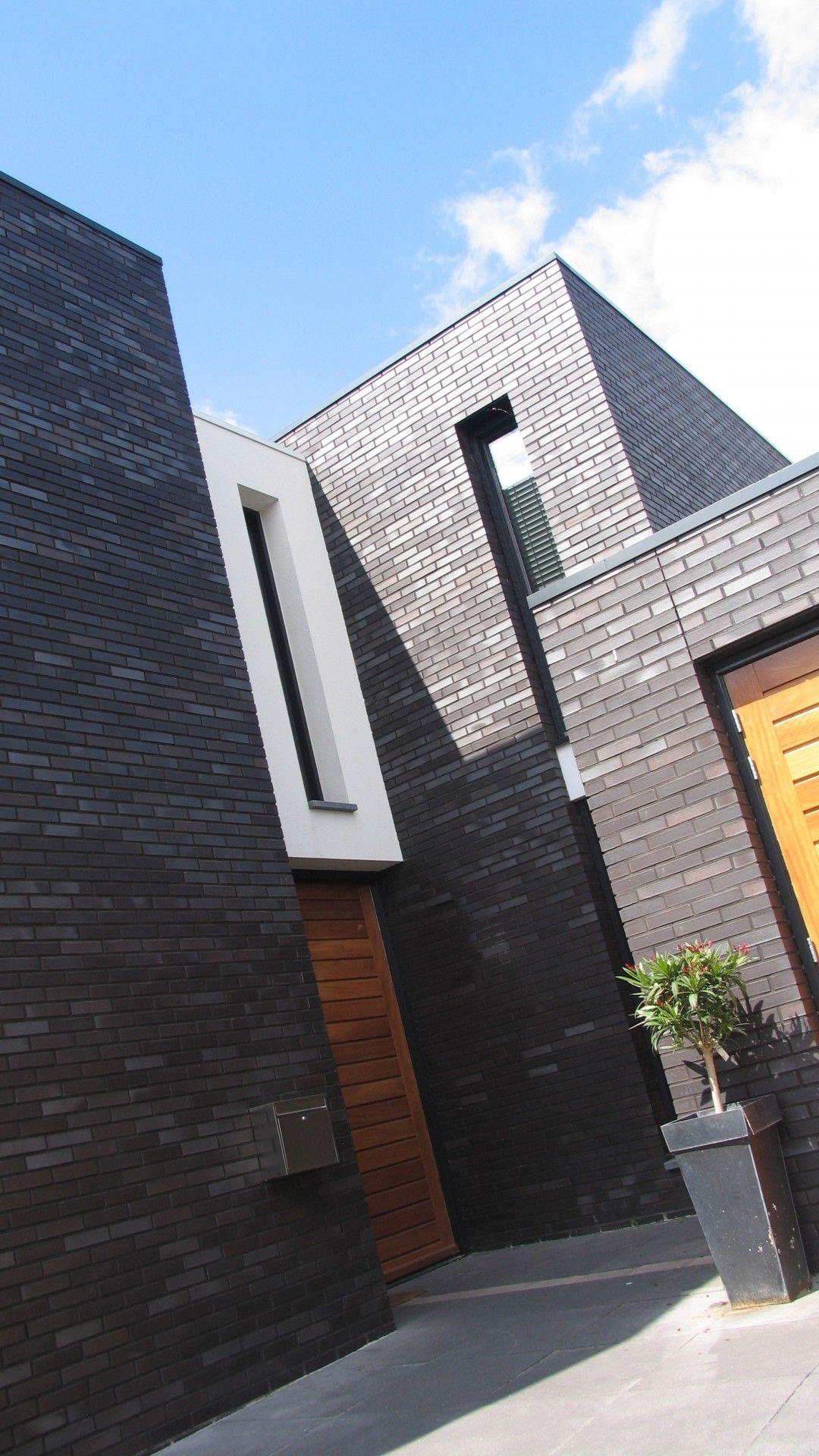 Moderne woning een ingetogen huis in strak donker metselwerk met stucwerk accenten en - Huis architect hout ...