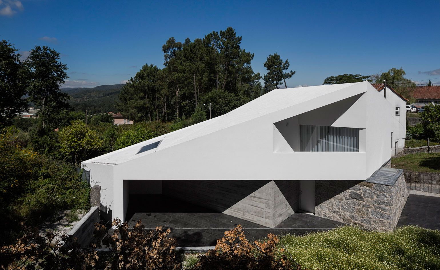 Modern Architectural Forms casa taíde balances a modern, angular addition over a granite