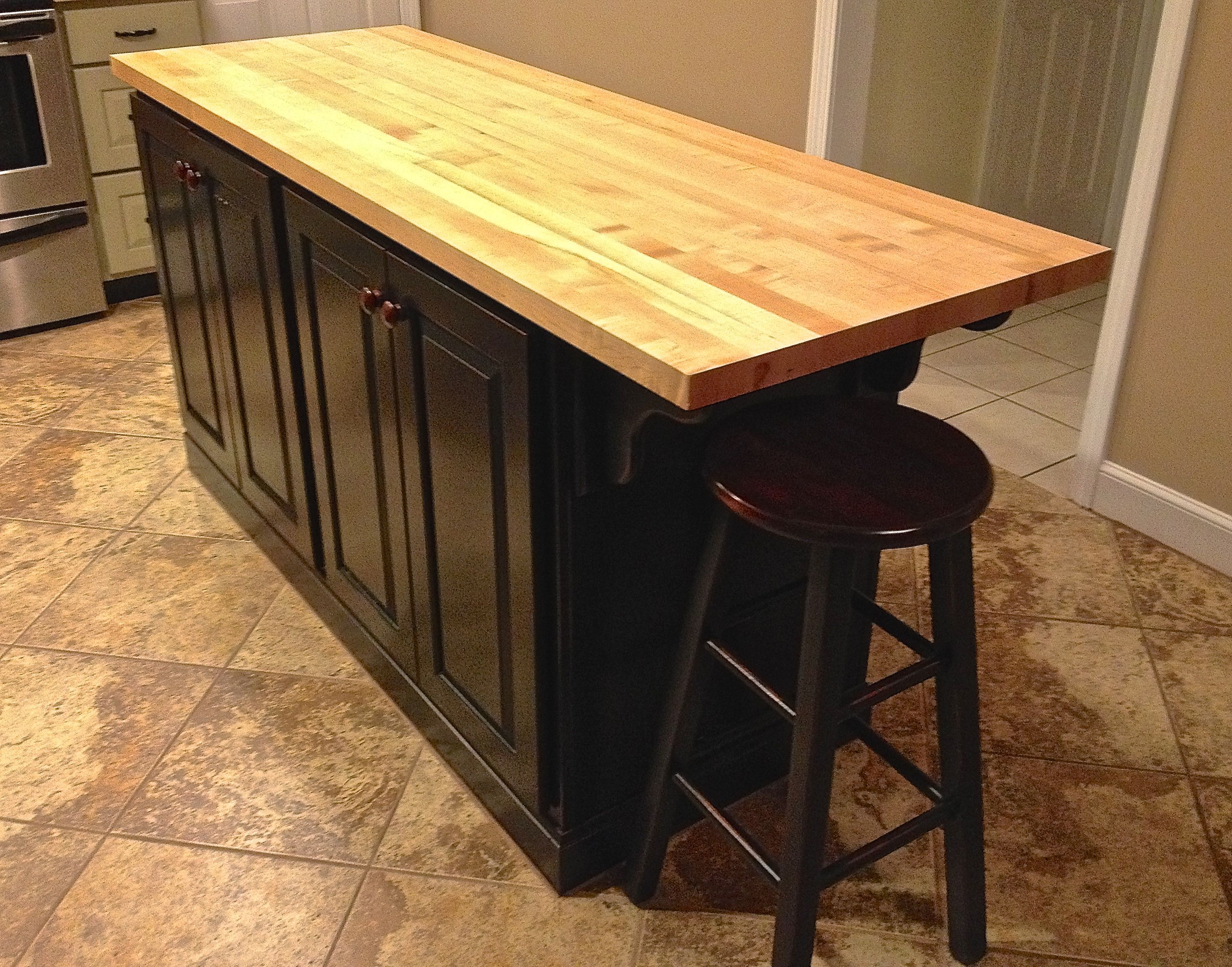 Black Distressed Island With A Maple Butcher Block Countertop In A