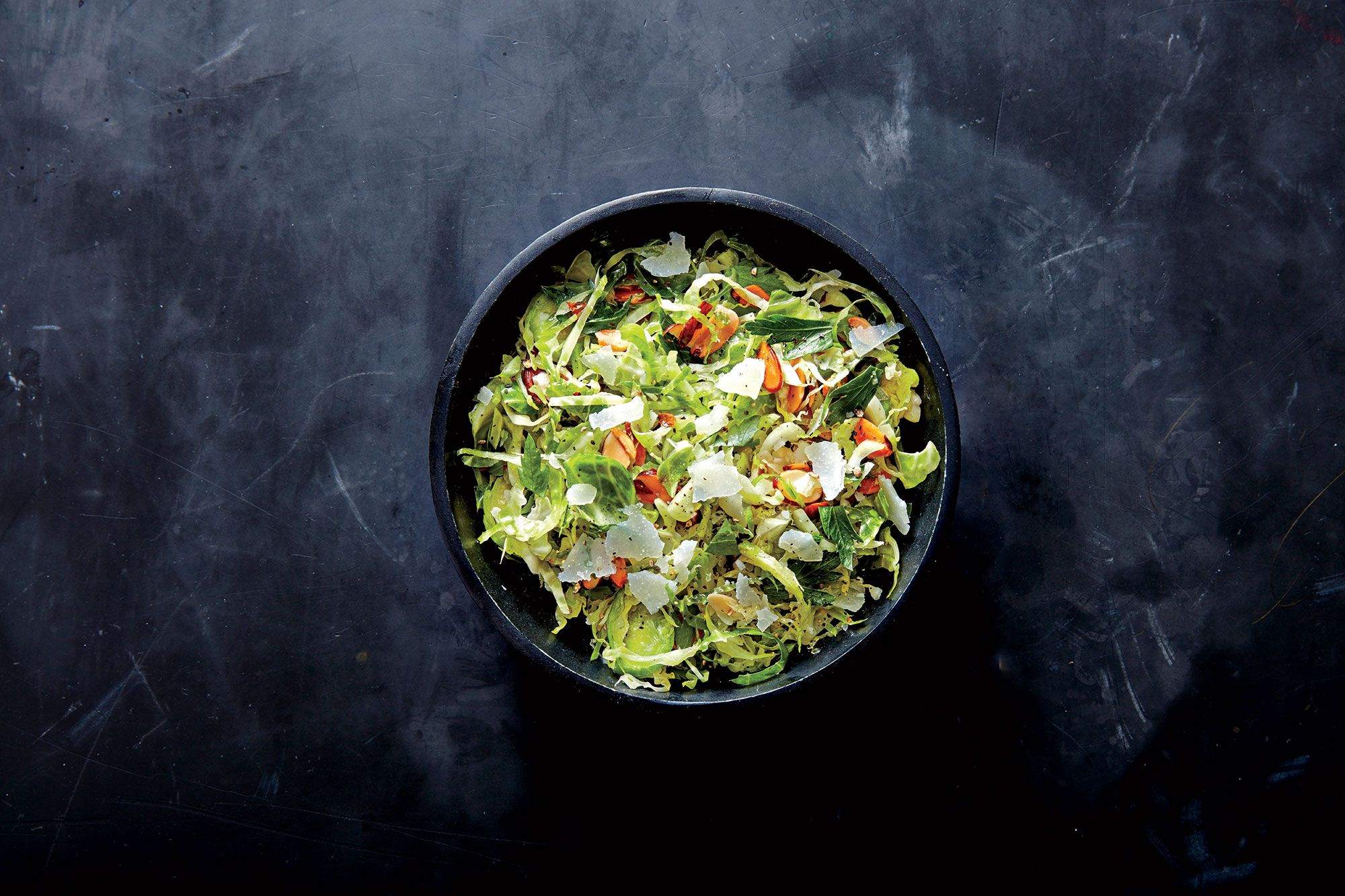 Caesar Brussels Sprouts Salad with Almonds | There's a bounty of prepared produce in the produce section of the supermarket these days, and we're happy to take advantage. Think of preshredded Brussels sprouts as fall's answer to coleslaw mix, and use it in salads, slaws, and quick sautés. If you can't find them, trim whole Brussels sprouts and thinly slice. Here the sprouts get the Caesar treatment, with a garlicky vinaigrette and toasted sliced almonds.
