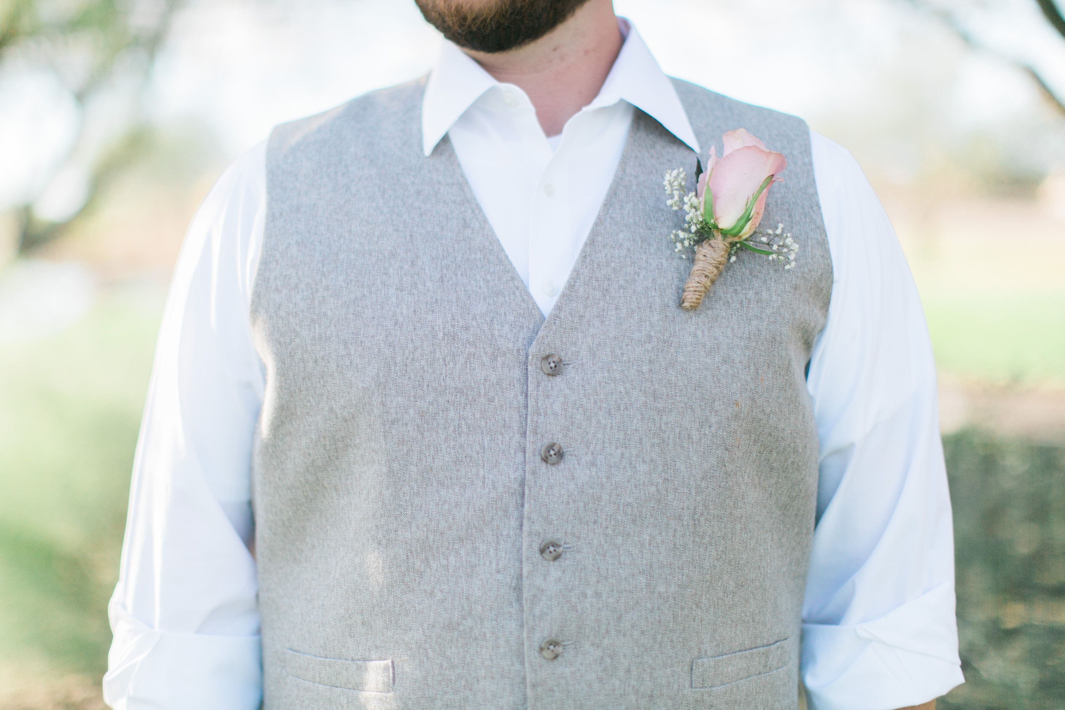 Groom in a light grey vest with a rolled up white buttoned down ...