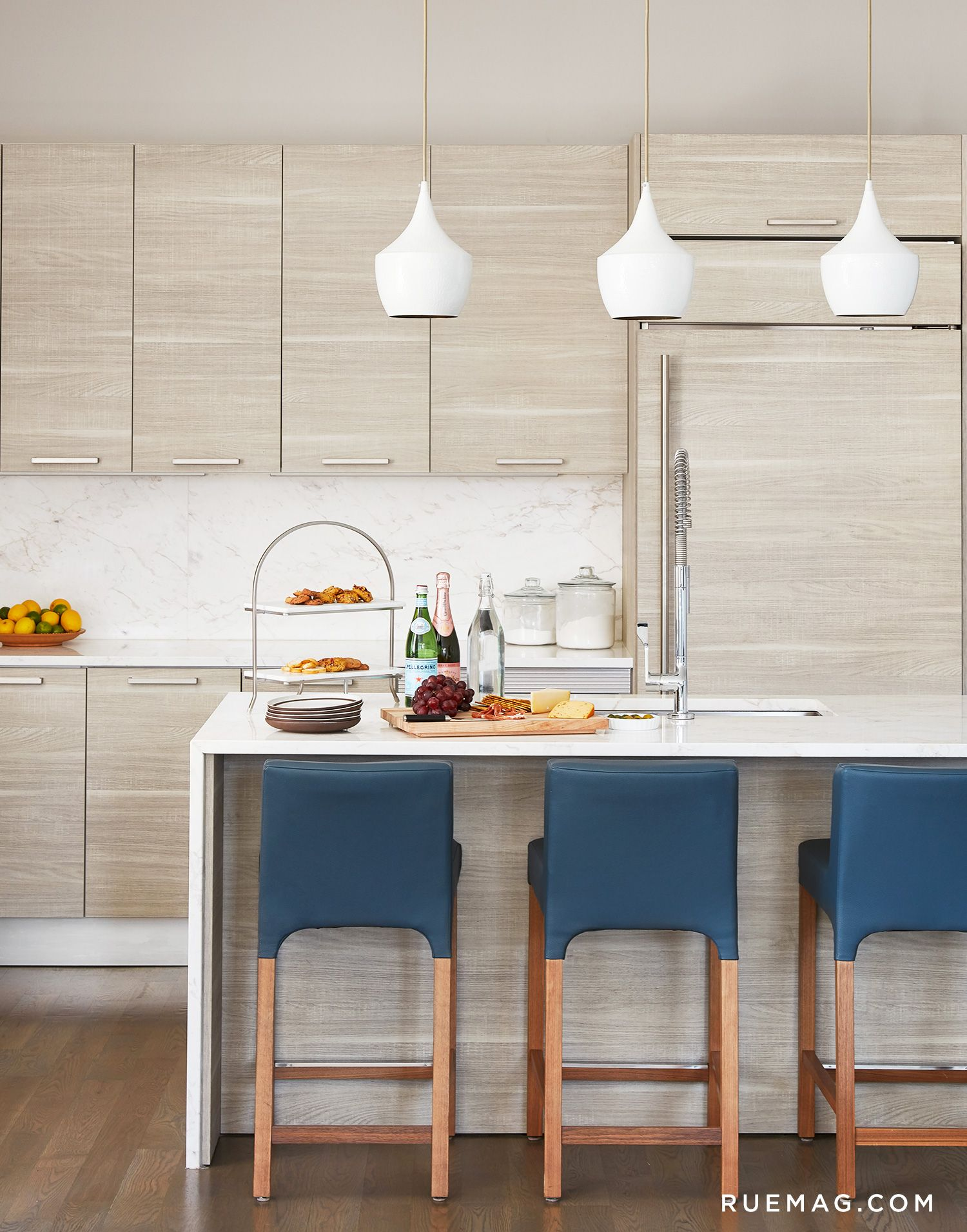 Sleek kitchen with blue leather bar stools and white pendant lights ...