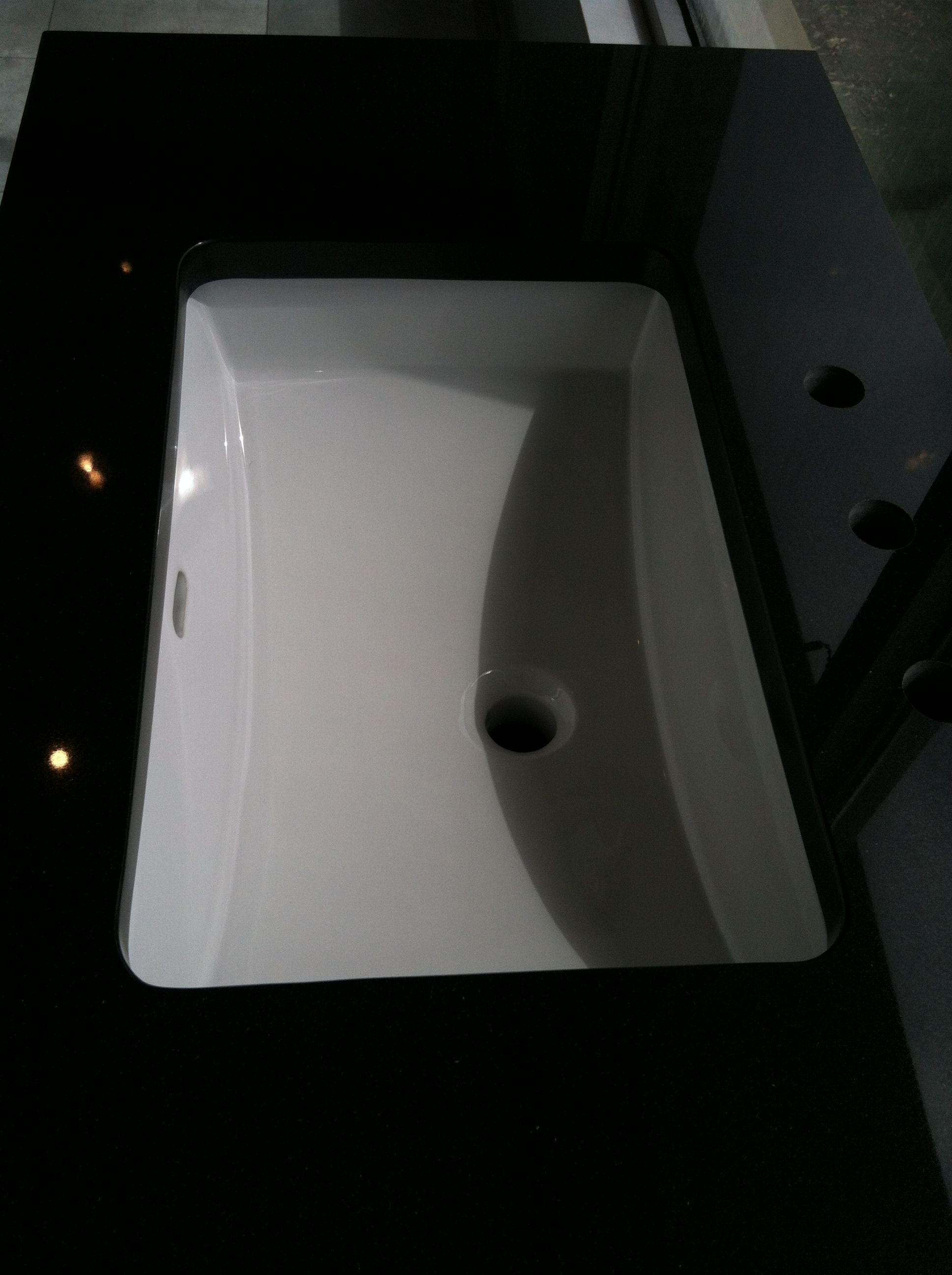 absolute black granite countertop and white sink for the ...
