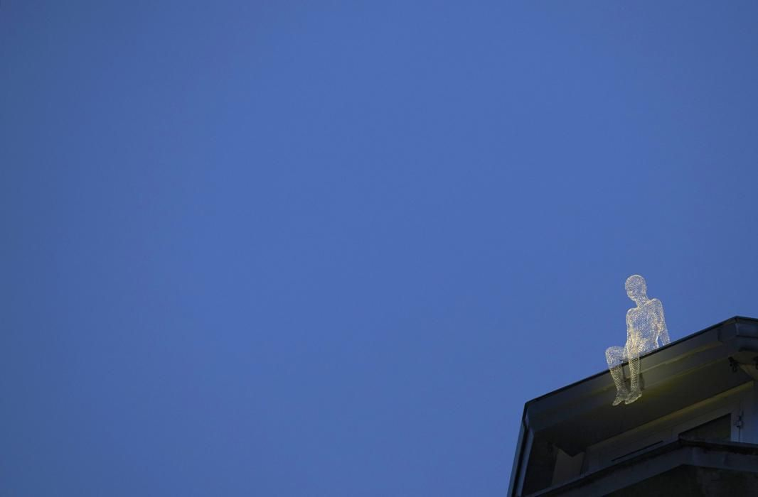 """An element of the installation """"Voyageurs"""" by French artist Cedric Le Borgne sits atop building top at Place Bel Air in Geneva December 1, 2014. The installation is part of the Geneva Lux Festival presenting four art installations in the town city centre until January 11, 2015. (REUTERS/Denis Balibouse)"""