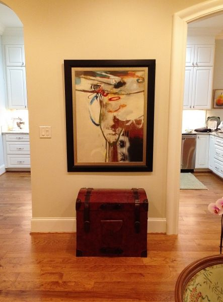A spare space in the living area gets a little attention with a great art piece, which is anchored by a trunk.