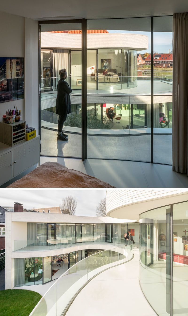 The floor to ceiling curved glass windows and doors on the upper floor of this modern house open up to the wraparound balcony