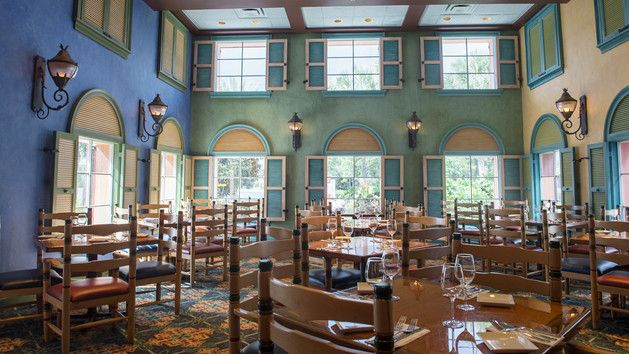 Disney Caribbean Beach Resort Shutters At Old Port Royale Open Lanterns And Large Windows Illuminating A Dining Room Filled With Chairs