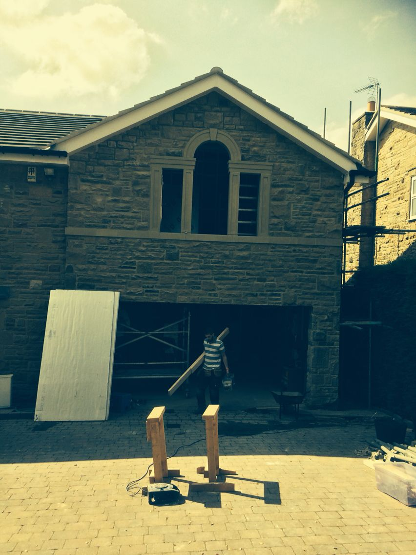Two storey random rubble stone extension with sawn stone band course and hand carved stone jambs mullions and arched head with key stone. 2014 Derry Construction Ltd.
