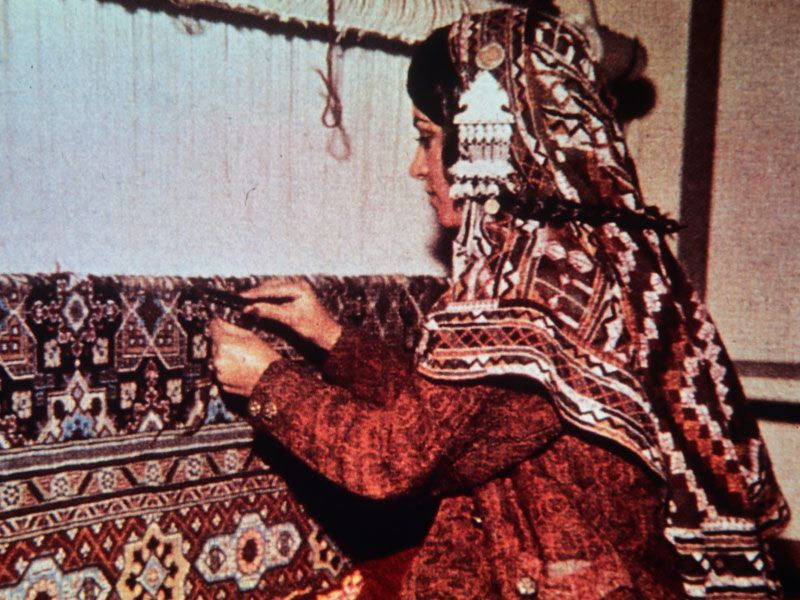 An Old Picture Of A Beautiful Woman Weaving Traditional Persian Rug