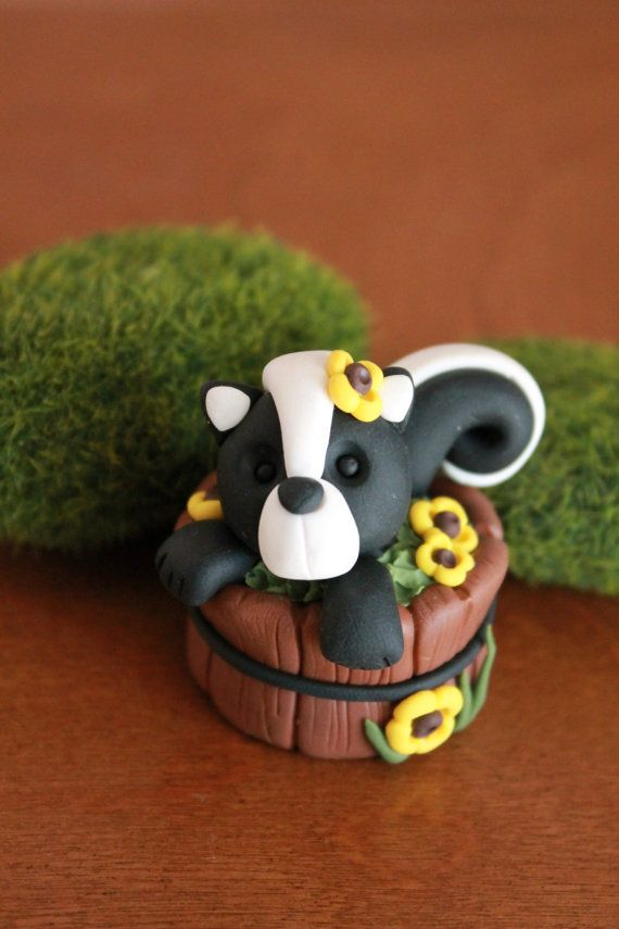 This listing is for an adorable hand sculpted polymer clay skunk in a wooden barrel surrounded by sunflowers! Cheery and bright, its guaranteed to get
