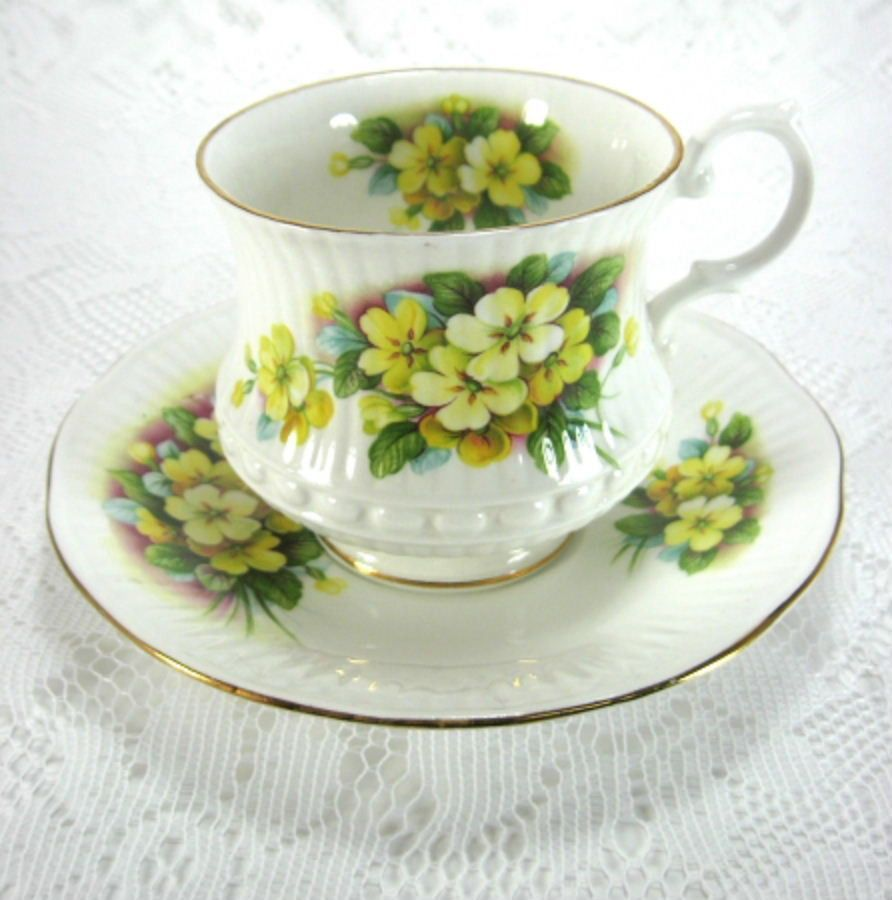 This is a pretty tea cup and saucer with a yellow primrose pattern on white bone china with gold trim by Royal Minster, England from the 1970s. The cup is 3 inches high and the saucer is 5.75 in diame