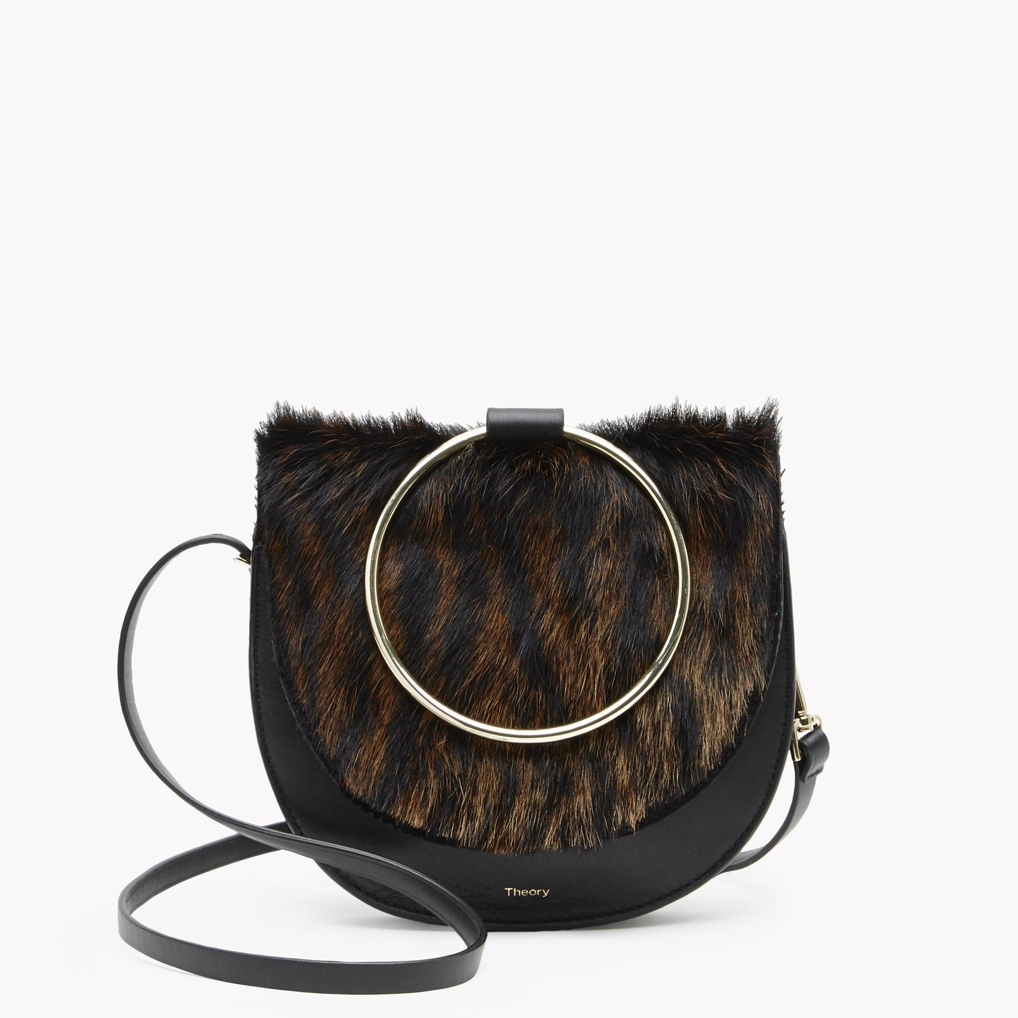 38c8ba1430f Our striking handbag featuring a brilliant 10kt gold-finished handle and  alluring curves emphasized with heavy edge stitching.