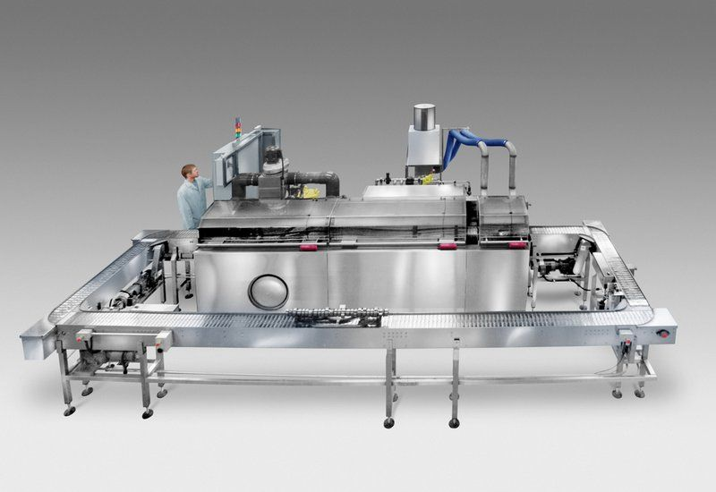 """Indexing conveyor washer with 14"""" wide continuous loop table-top chain belt, designed to clean diesel engine camshafts in manufacturing process; has pick & place load/unload."""