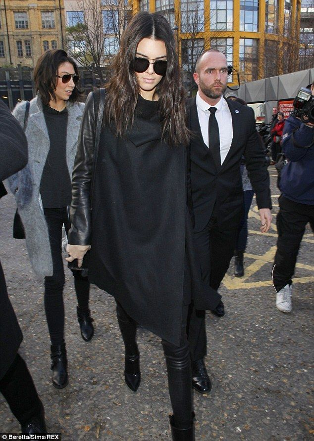 Kendall Jenner Black Jacket, Black Pant, Black Shawl/Poncho, Shoes (black: heels, ankle boots, or heels), center-parted Wavy hair, and black accessories.