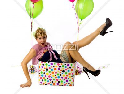 female with mouth open sitting in a box. - Female with mouth open sitting in a box with balloons on the side over white background, Model: Carrie Galbraith