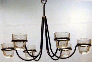 This black wrought iron votive chandelier hangs over the head of the this black wrought iron votive chandelier hangs over the head of the black wrought iron bed mozeypictures Choice Image
