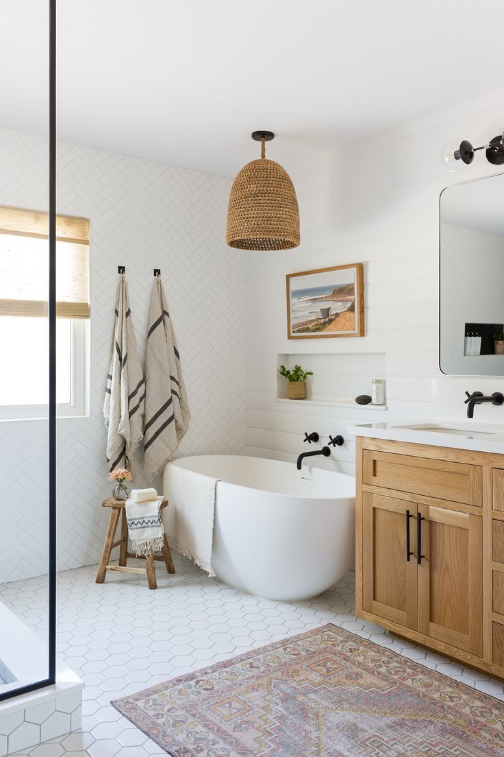 A large and spacious master bathroom with light wood, white tile, and a great tub. #homedecor #bathtub #freestandingtub #coastalstyle
