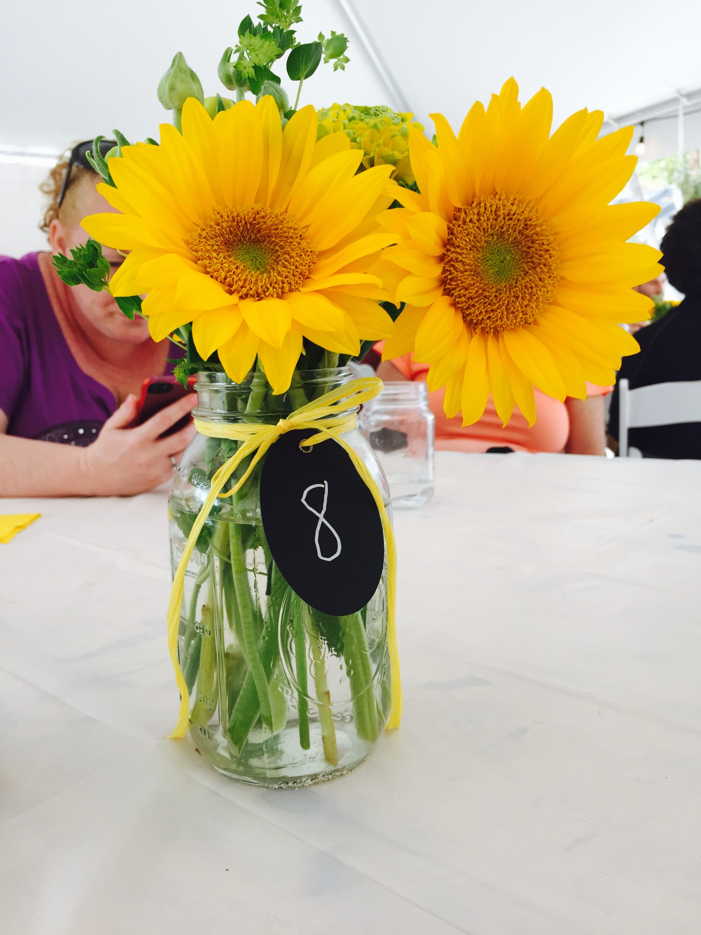 Fresh cut yellow flowers with yellow raffia and chalkboard table
