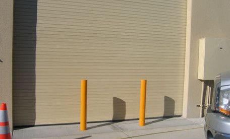 Fixed security bollards are placed in front of this facility entrance to protect against high-speed vehicle collisions. #buildingsecurity #bollards #trafficguard