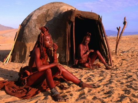 Himba women by a traditional hut ... Kaokoveld, Kunene, Namibia  Living in a faraway part of the country (Kaokoveld) with few touristic resorts or none.