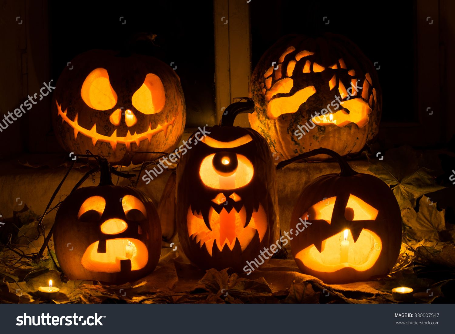 Photo Composition From Five Pumpkins For Halloween. Jack, Hands, Crying, A Cyclops And Frightened Pumpkins Against Autumn Leaves And Candles - 330007547 : Shutterstock