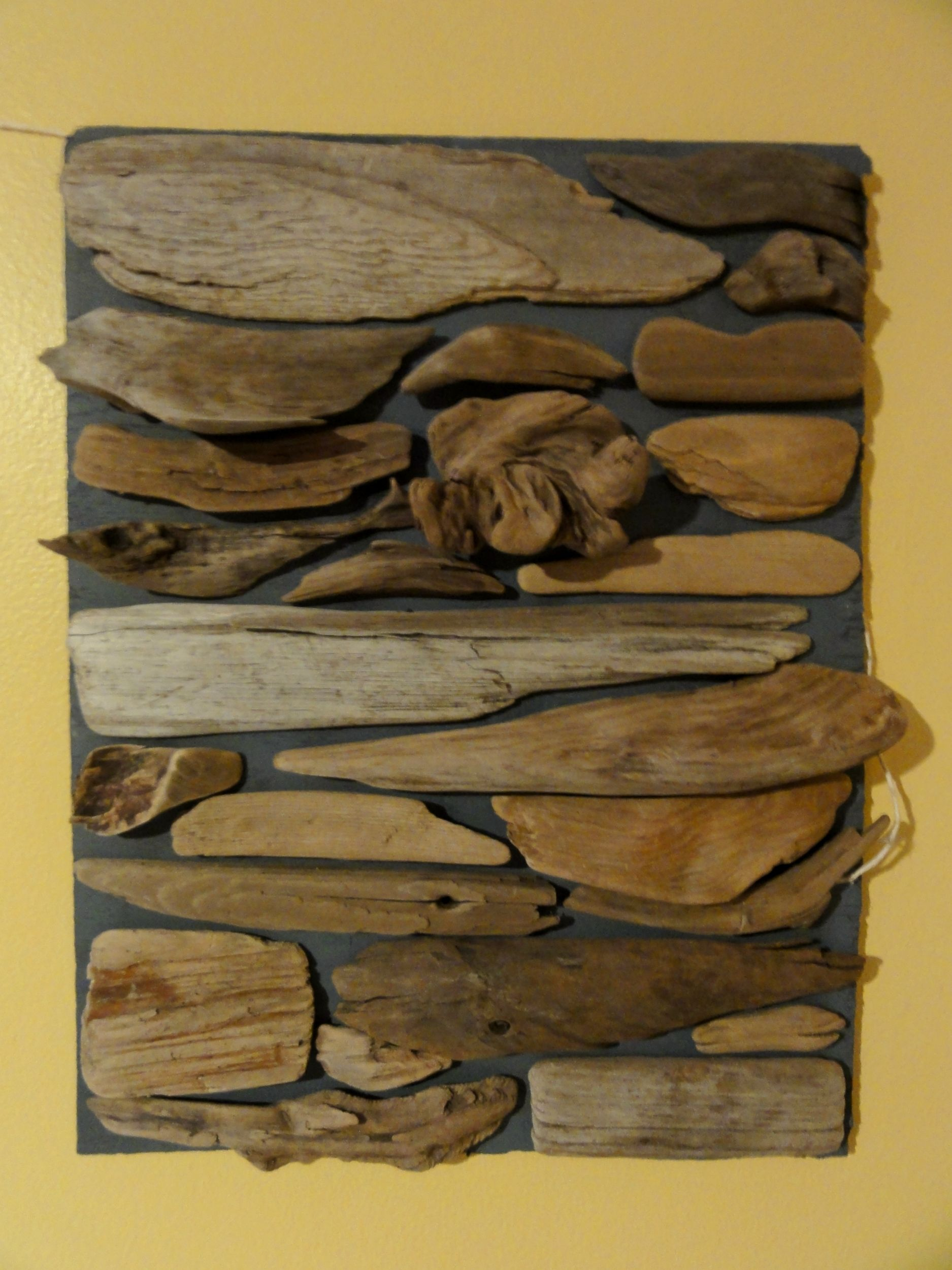 Diy driftwood wall art paint desired sized board with favored colors gather assorted pieces of driftwood and arrange to fit together glue wood on