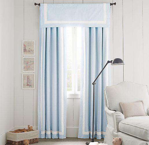 Pale blue curtains with white ribbon trim.