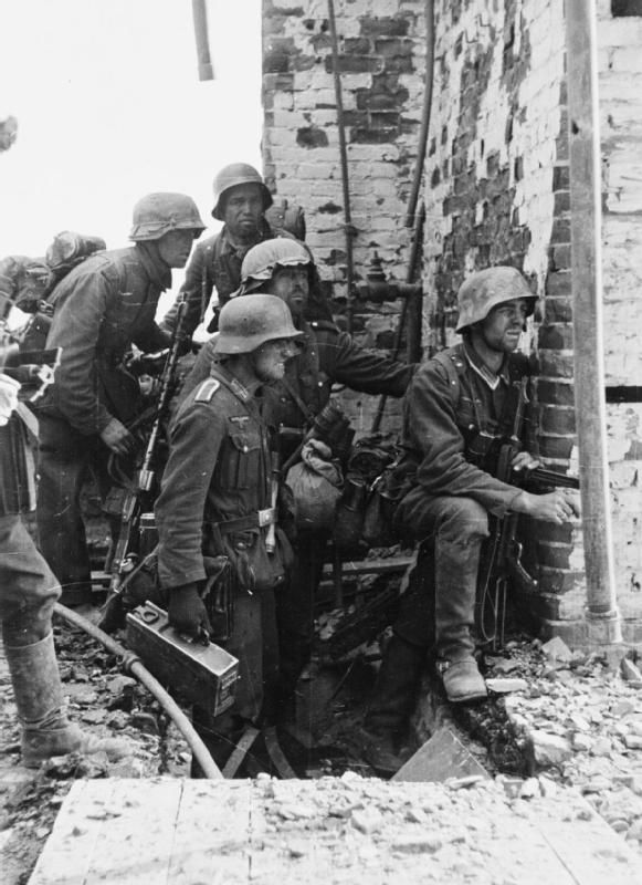 A group of German infantry takes shelter behind a wall during heavy street fighting in Stalingrad.