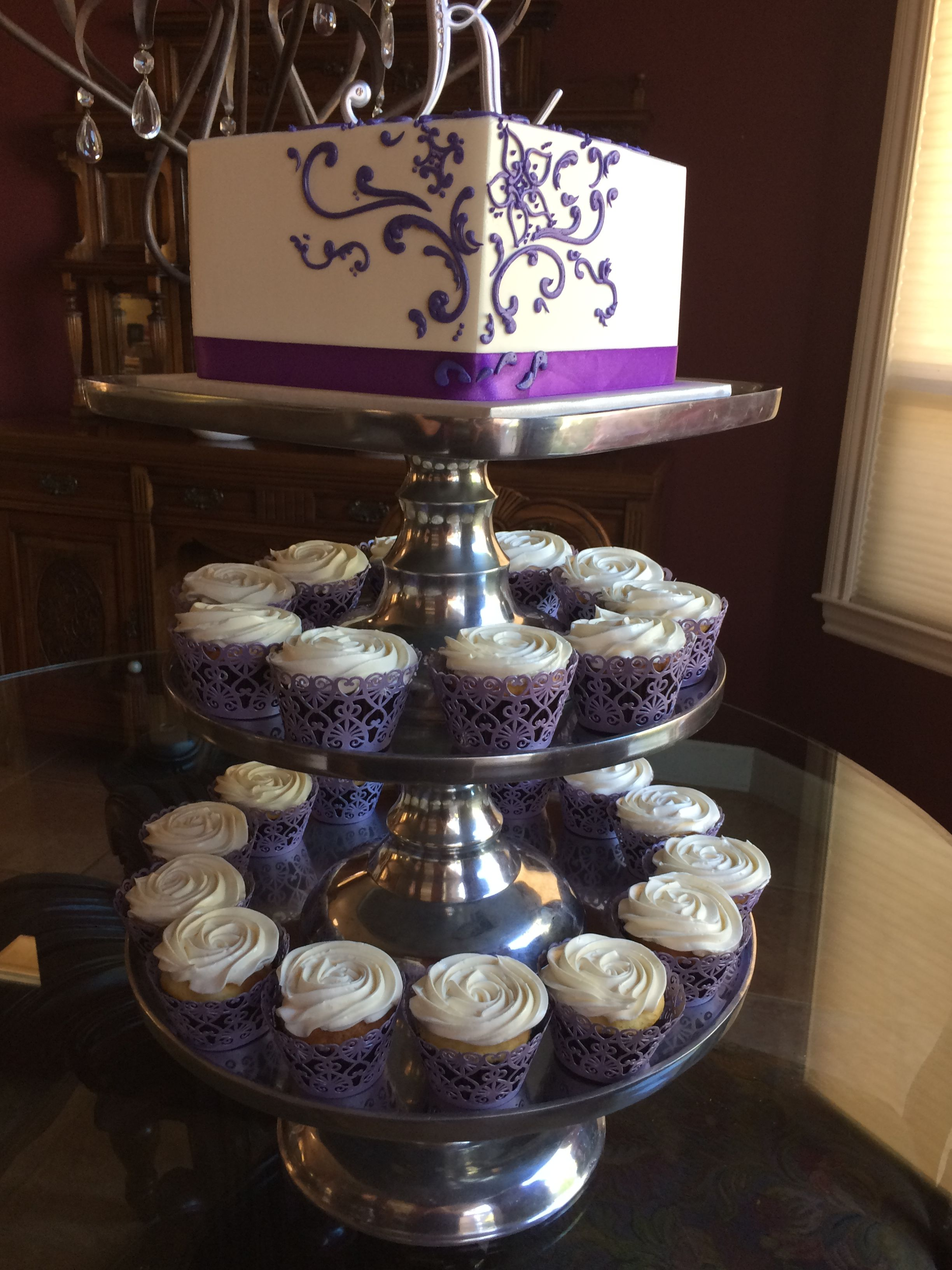 Square wedding cake with purple scrolling and rosette cupcakes