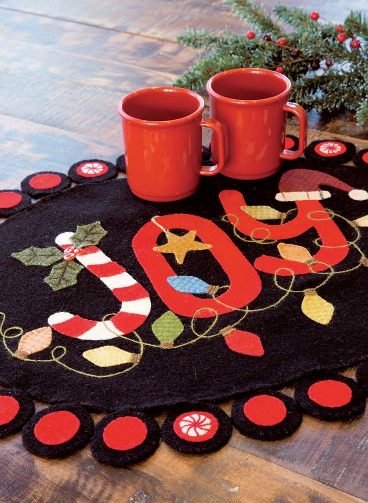 JOY quilted table topper: This fun and festive wool table topper was designed by Paula Stoddard. Made with fusible applique and finished off with assorted embroidery stitches, it is sure to be a holiday favorite!
