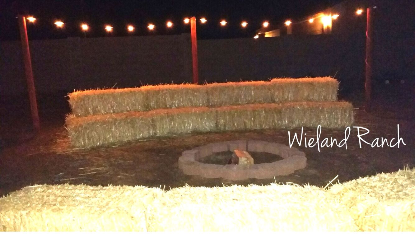 Straw bale, hay bale seating around our fire pit. Country western backyard remodel. Outside lighting on wooden poles.