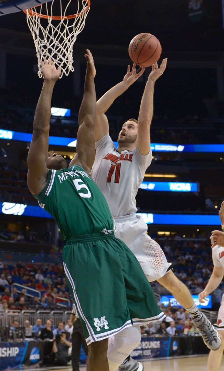 Louisville forward Luke Hancock (11) drives to the basket as Manhattan center Rhamel Brown (5) defends in a second-round game in the NCAA co...