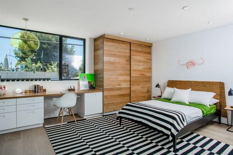 Chambre adulte avec lit deux places tapis rayé noir et blanc et
