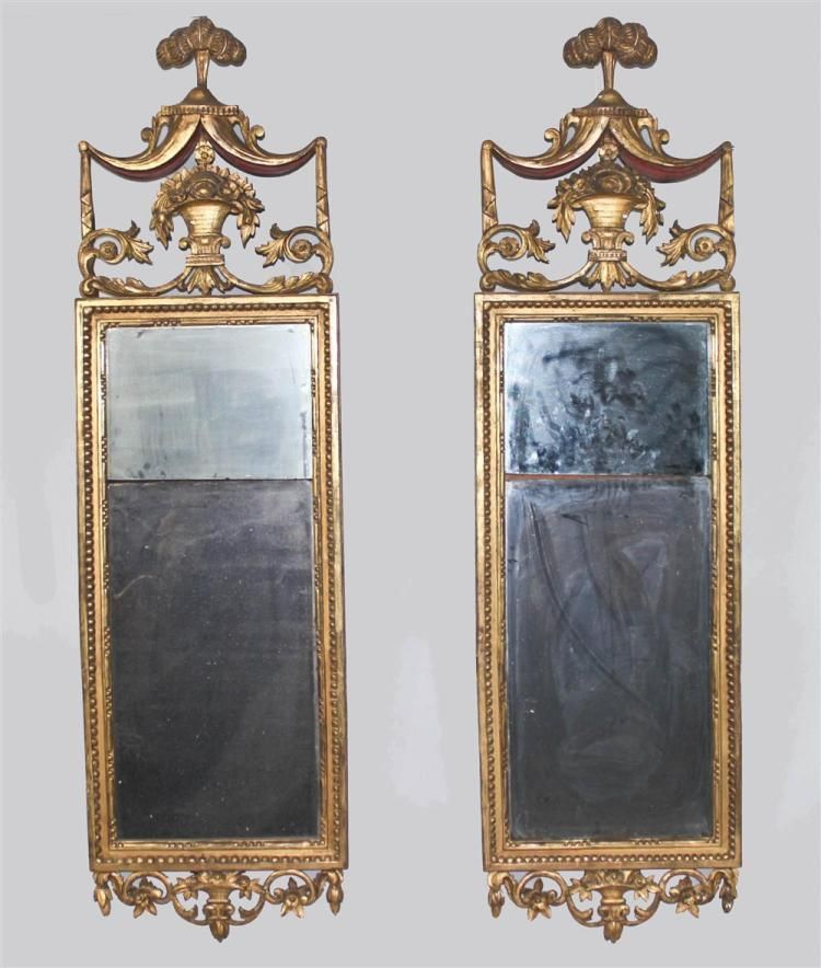 <b>PAIR OF NORTHERN ITALIAN CARVED GILTWOOD LOOKING GLASSES, CIRCA 1800</b> having water-gilded rectangular frame incorporating a canopy-draped crest with plumed finial above a flower-filled basket with scrolled leaf base; the mirror plate in two parts, the lower section with beveled edge, enclosed by beaded frame with flower-filled basket and scrolling decoration below (2) - h:63w:18in. <br />  <br /> Provenance: Property from the Du...