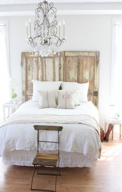 Old worn doors stand in for a charming Shabby Chic headboard ... everything about this bedroom has my name on it - chair, chandelier, bed linens, etc.  @ Cady Chandler Fontenot.