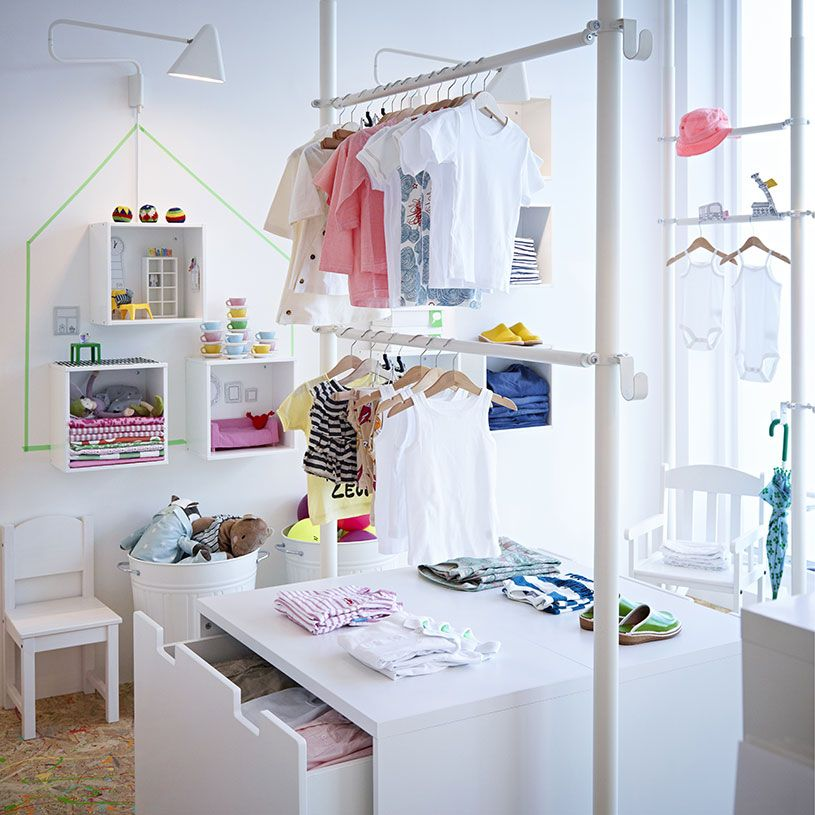 A boutique for childrens clothes with white display shelves and