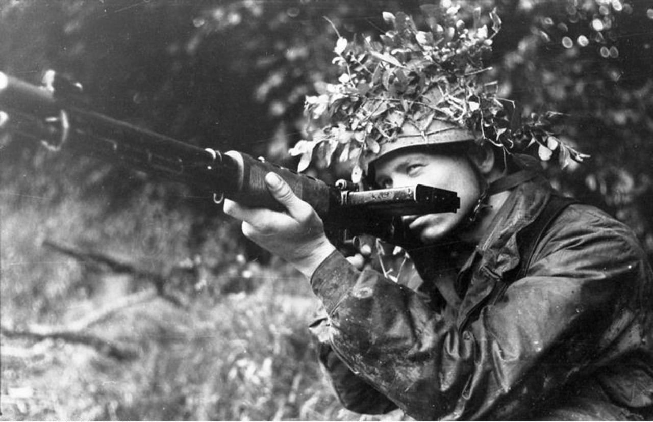 """A German Fallschirmjäger (""""paratrooper"""") poses with his uncommon, early model Walther FG42 (Ausführung """"C"""") during the battle for Caen in lower Normandy, photographed by Wolfgang Vennemann (June 21, 1944). Note the magazine protruding from the left side of the weapon."""