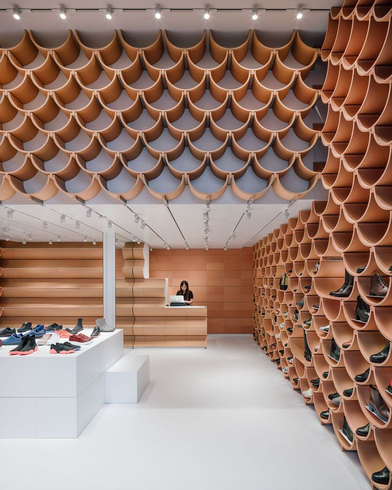 Inside this modern retail store, the pattern on the walls is revealed to be made up of roof-tile like ceramic elements, that neatly complement each other. #RetailStore #StoreDesign #Ceramic #CeramicShelves