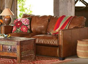 Rustic leather couch with feminine pillow & decorative throw ...