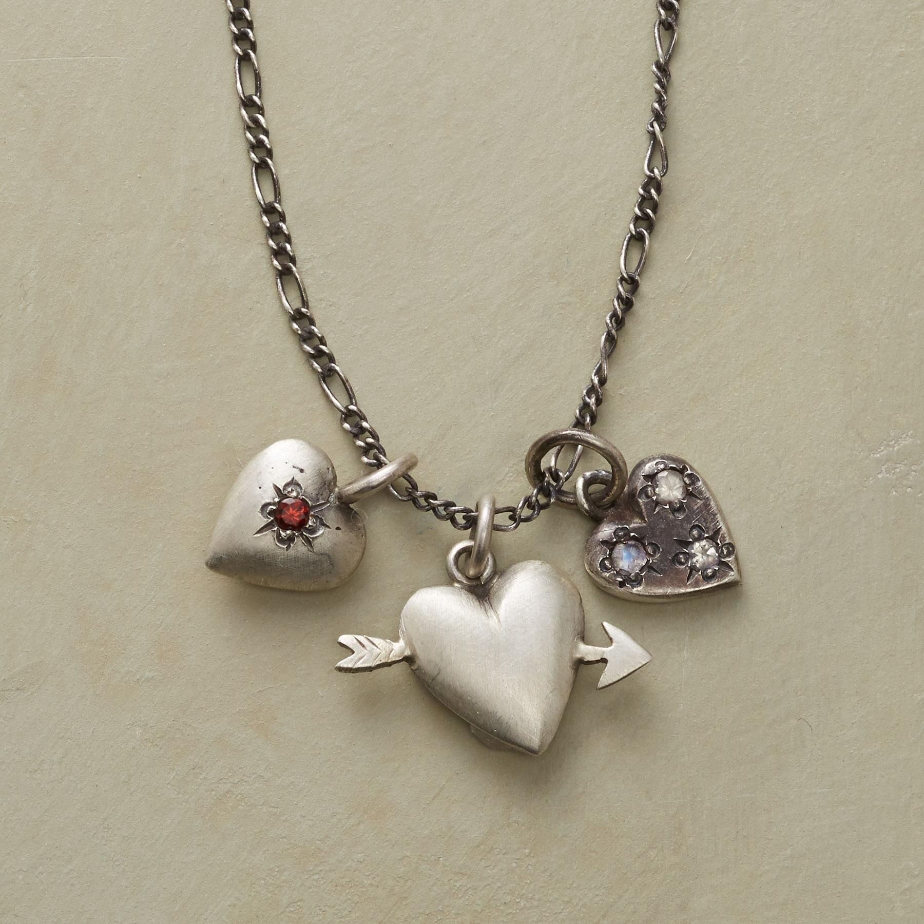 """VINTAGE HEARTS NECKLACE--Jane Diaz crafts a trio of hearts in burnished sterling silver, one set with garnet, another with rainbow moonstone, the last pierced with Cupid's arrow. Oxidized sterling silver chain, spring ring clasp. Catalog exclusive. 18""""L."""