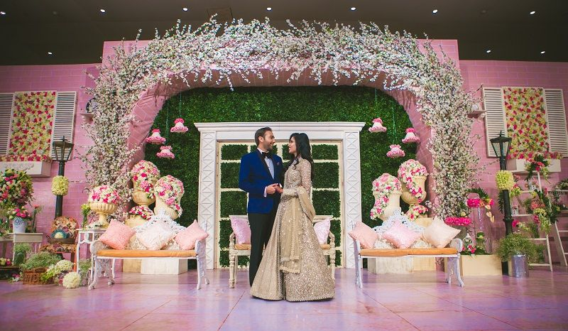 Stage decorated with clustered floral arrangements strings just stage decorated with clustered floral arrangements strings just like an indoor dreamy setup whimsical green wall decorindian wedding junglespirit Image collections