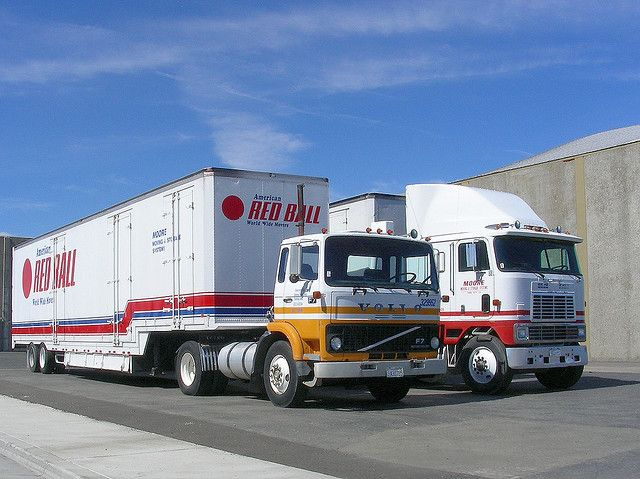Volvo and International tractors pulling moving van trailers