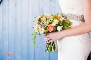 A classic rose wedding bouquet deserves a photo on its own, especially when paired with a stunning champagne embellished sash for the wedding dress.| Ivory Orchid Photography in Tucson, AZ