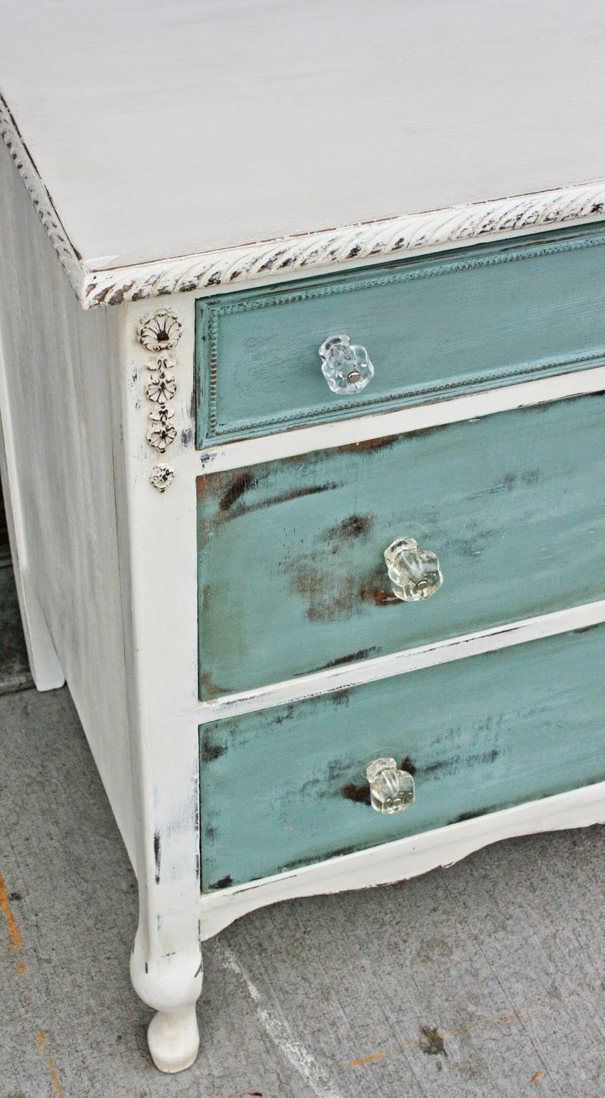 Antiqued white with sea blue drawers distressed. I love the glass ...