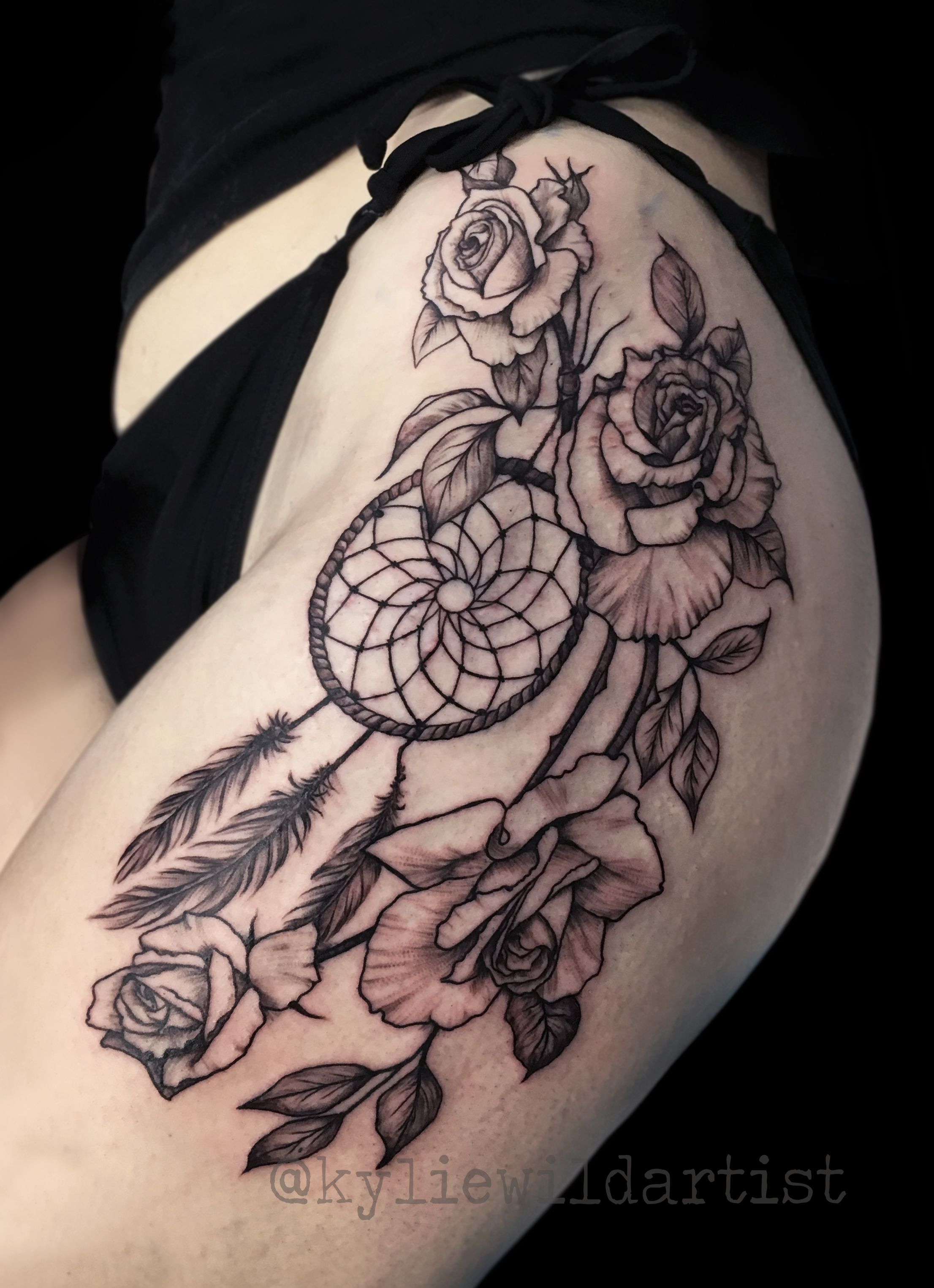 Roses and a dream catcher thigh tattoo in black and grey by kylie