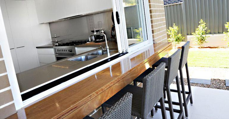Wisdom Homes kitchen window opens out to lanai area kitchen