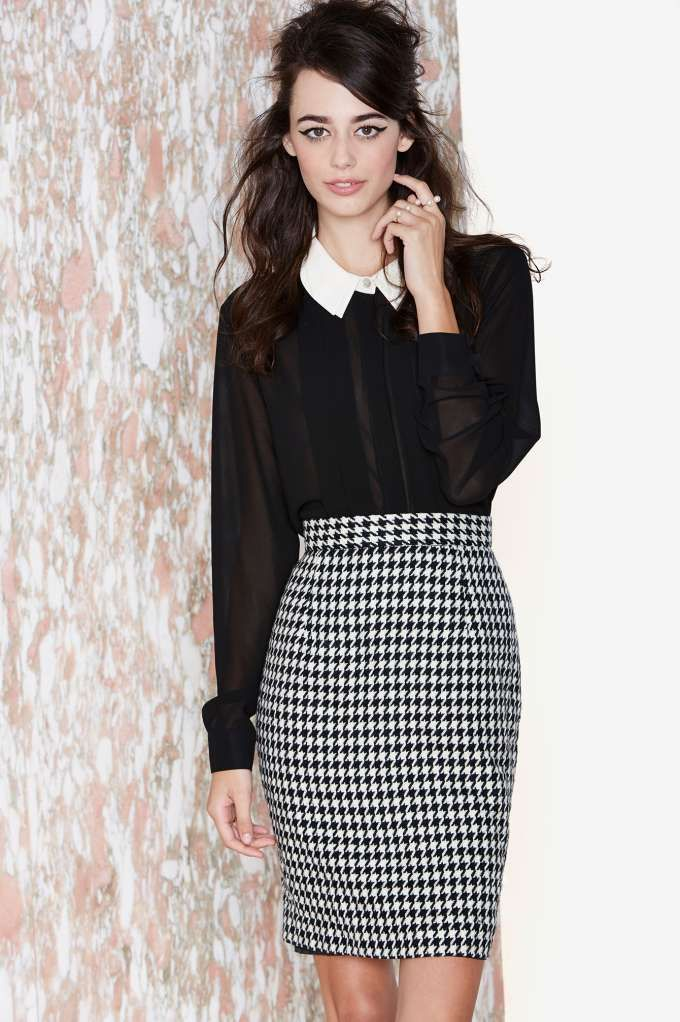 We're obsessed with this vintage black and ivory skirt with a houndstooth print, gold metallic threading, and a zip closure at back.