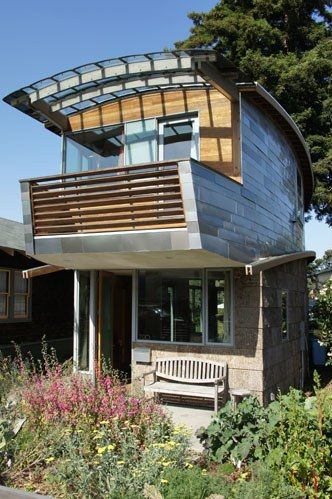 Architect Karl Wanaselja and partner Cate Leger created a unique small house in Berkeley, California.  They call it the McGee House. It consists of 104 salvaged car roofs which cover the upper side walls of the home. The inspiration behind the upper siding came from fish scales.  The lower wall siding is made out of a waste product from the furniture industry in clad form called poplar bark.  The awnings are side windows from America's best-selling minivan, the Dodge Caravan.  It's a 2…