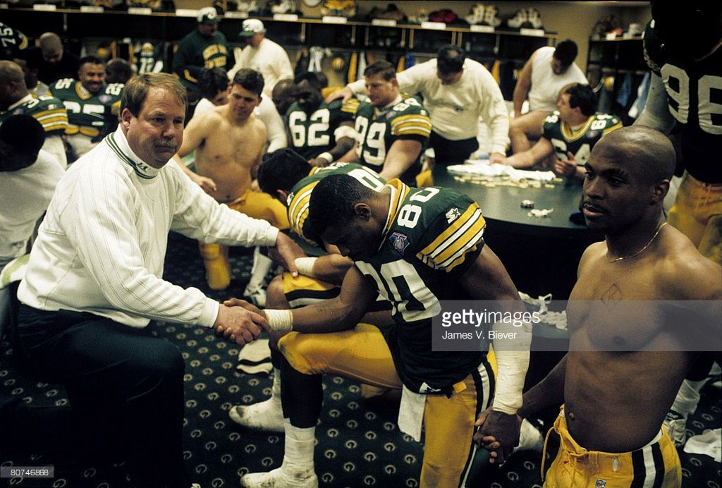 Green Bay Packers head coach Mike Holmgren joins his team in a post game prayer in the locker room following the Packers 16-12 victory over the Detroit Lions in the 1994 NFC Wild Card Playoff Game on December 31, 1994 at Lambeau Field in Green Bay, Wisconsin. (Photo by James V. Biever/Getty Images)
