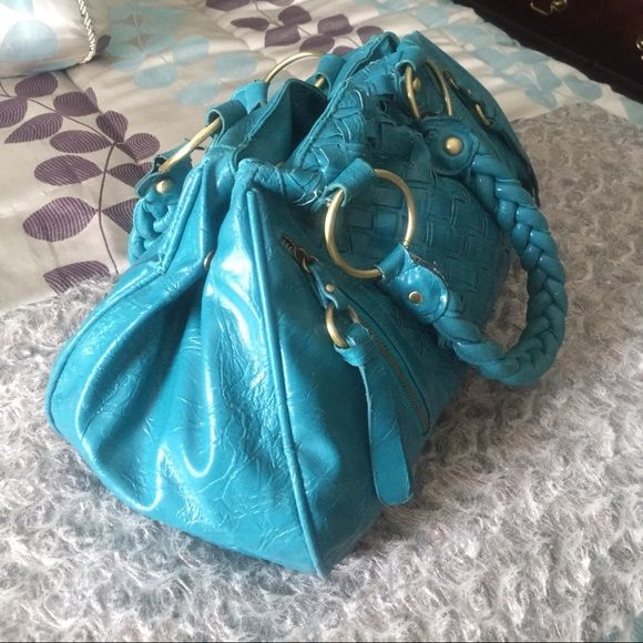 Turquoise Leatherette Purse This fun and stylish bag is the perfect year-long staple to add in your closet. The braided handles are sturdy and there is plenty of space inside the purse without it being too bulky. Magnetic snap closures allow the bag to be closed at the top; snap closures are on both sides of the bag for a more compact look. Forever 21 Bags
